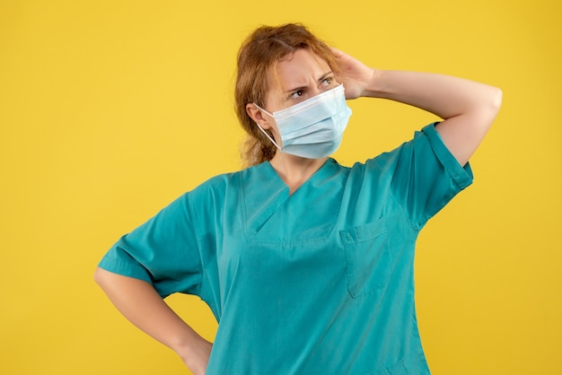 Vorderansicht der ärztin in der sterilen schutzmaske auf gelber wand