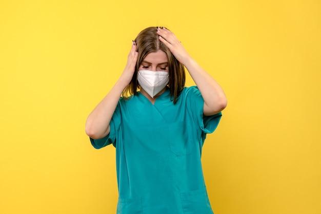 Vorderansicht der ärztin mit maske auf gelbem boden-emotionsvirus-pandemiekrankenhaus