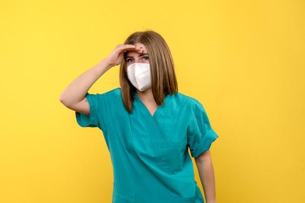 Vorderansicht der ärztin mit maske auf gelber wand