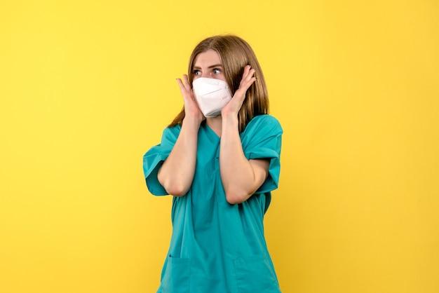 Vorderansicht der ärztin mit steriler maske auf gelber wand