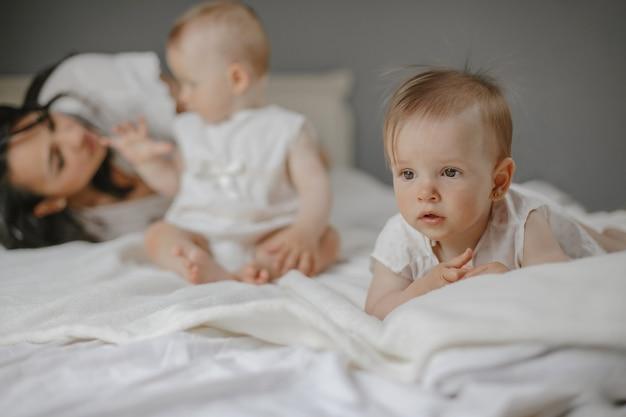 Vorderansicht der alleinerziehenden mutter, die mit zwillingsmädchen im schlafzimmer spielt.
