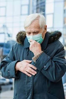 Vorderansicht der alten frau in der stadt, die medizinische maske trägt und sich krank fühlt