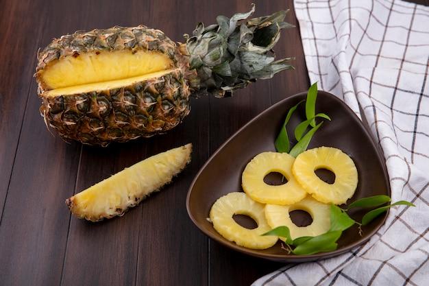 Vorderansicht der ananas mit einem stück aus ganzen früchten und einer schüssel ananasscheiben auf kariertem stoff und holzoberfläche