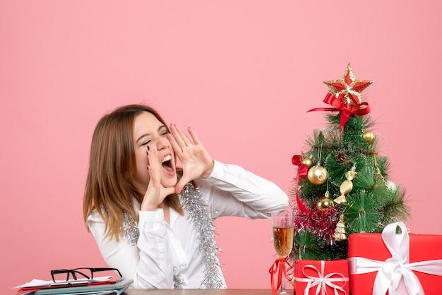 Vorderansicht der arbeiterin, die hinter ihrem tisch mit geschenken sitzt, die laut rosa anrufen