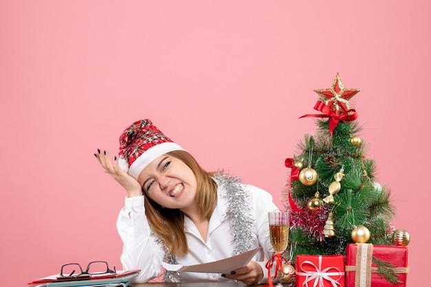 Vorderansicht der arbeiterin, die um weihnachtsatmosphäre auf rosa sitzt