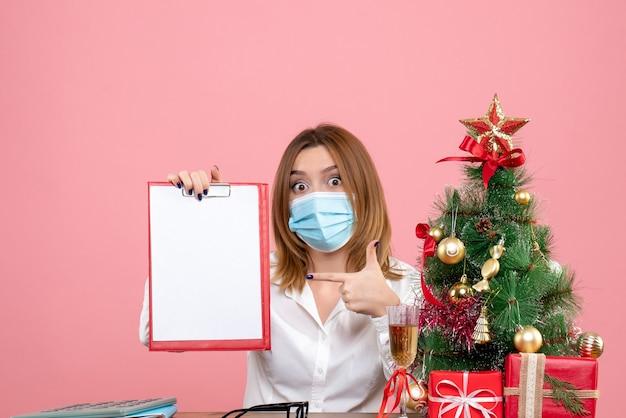 Vorderansicht der arbeiterin in der maske, die aktennotiz auf rosa hält
