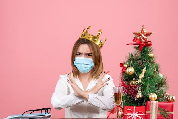 Vorderansicht der arbeiterin in der sterilen maske mit krone auf rosa