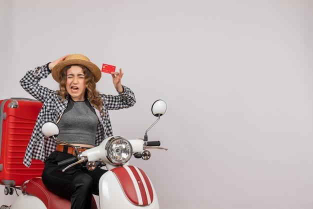 Vorderansicht der aufgeregten jungen frau auf moped, das karte auf grauer wand hält