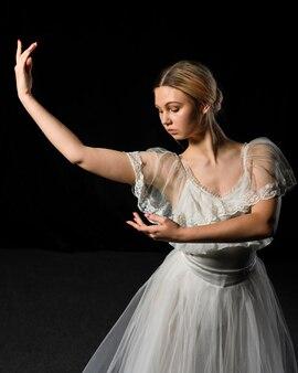 Vorderansicht der ballerina aufwerfend im ballettröckchenkleid