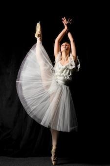 Vorderansicht der ballerina im ballettröckchenkleid mit dem bein oben