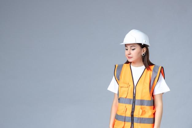 Vorderansicht der baumeisterin in uniform auf grauer wand