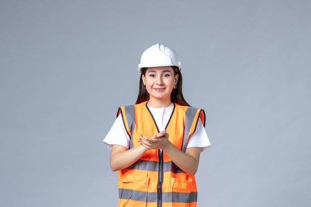 Vorderansicht der baumeisterin in uniform, die auf graue wand klatscht