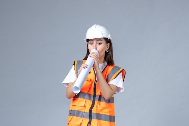 Vorderansicht der baumeisterin in uniform mit poster in den händen auf weißer wand