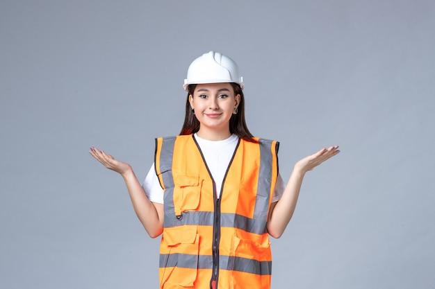 Vorderansicht der baumeisterin in uniform und schutzhelm auf grauer wand