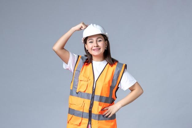 Vorderansicht der baumeisterin in uniform und schutzhelm lächelnd auf grauer wand