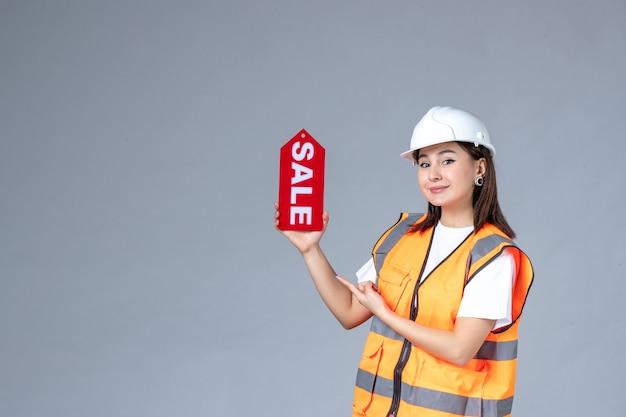 Vorderansicht der baumeisterin mit rotem verkaufsbrett auf weißer wand
