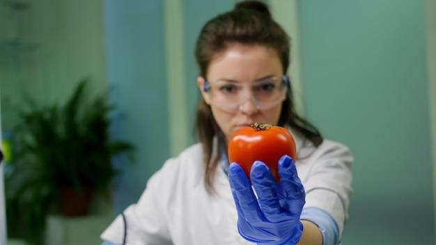 Vorderansicht der biologen-forscherin, die pfeffer analysiert, der mit chemischer dna für wissenschaftliche landwirtschaftsexperimente injiziert wurde. pharmazeutischer wissenschaftler, der im mikrobiologielabor arbeitet