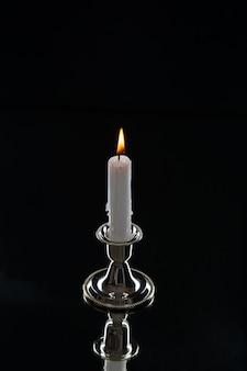 Vorderansicht der brennenden kerze im goldenen stand auf dunkler oberfläche