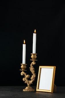 Vorderansicht der brennenden kerze mit bilderrahmen als speicher auf dunkler oberfläche