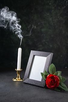 Vorderansicht der brennenden kerze mit bilderrahmen auf dunkler oberfläche