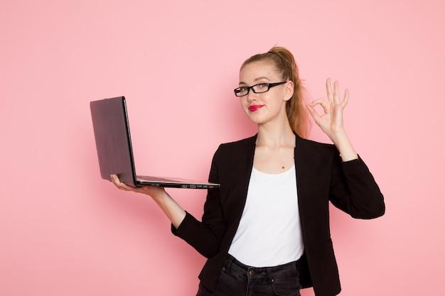 Vorderansicht der büroangestellten in schwarzer strenger jacke, die laptop an der hellrosa wand hält und verwendet
