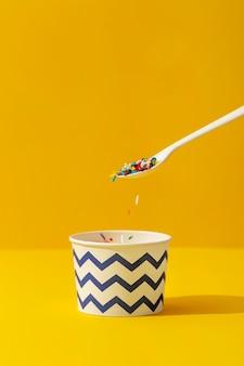 Vorderansicht der bunten streusel in der tasse mit löffel