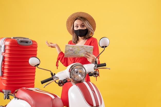 Vorderansicht der charmanten jungen dame mit schwarzer maske, die karte nahe moped hält