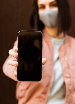 Vorderansicht der defokussierten frau mit gesichtsmaske, die smartphone hält