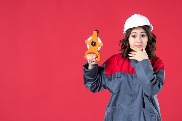 Vorderansicht der denkenden architektin in uniform mit schutzhelm, der maßband auf isoliertem rotem hintergrund hält