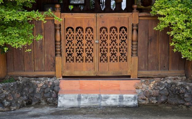 Vorderansicht der eingangsholz geschnitzten tür, thailändische art