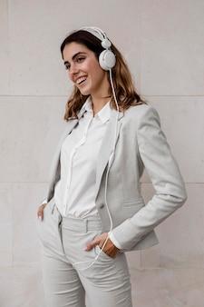 Vorderansicht der eleganten geschäftsfrau, die musik auf kopfhörern hört