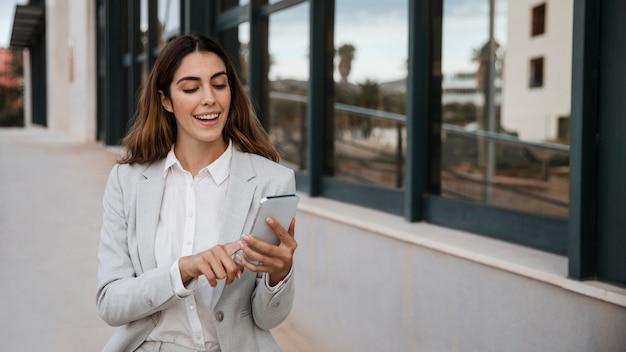 Vorderansicht der eleganten geschäftsfrau unter verwendung des smartphones in der stadt
