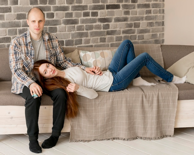 Vorderansicht der eltern, die auf couch sitzen