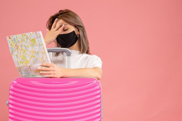 Vorderansicht der enttäuschten jungen frau mit schwarzer maske, die karte hält