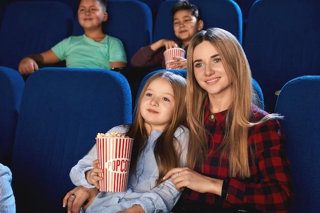 Vorderansicht der familie, die zeit zusammen im kino verbringt. attraktive junge mutter und kleine tochter, die sich umarmen und lächeln, während sie film schauen und popcorn essen