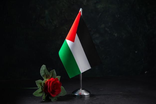 Vorderansicht der flagge palästinas mit roter blume auf schwarz