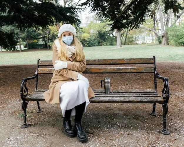 Vorderansicht der frau auf der bank im park während des winters, der medizinische maske trägt