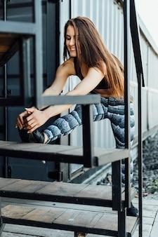 Vorderansicht der frau ausdehnend auf treppenhaus
