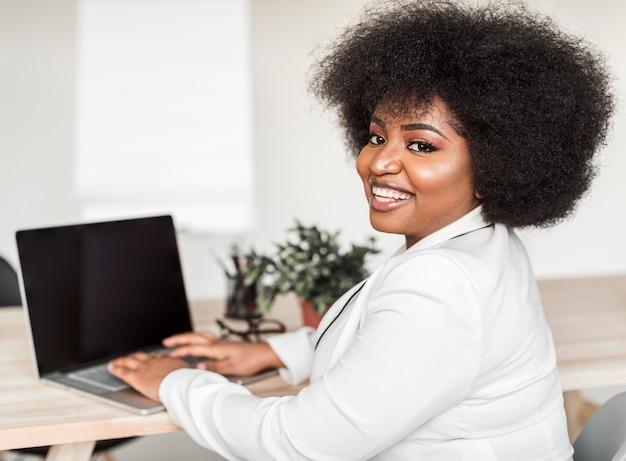 Vorderansicht der frau, die am laptop arbeitet