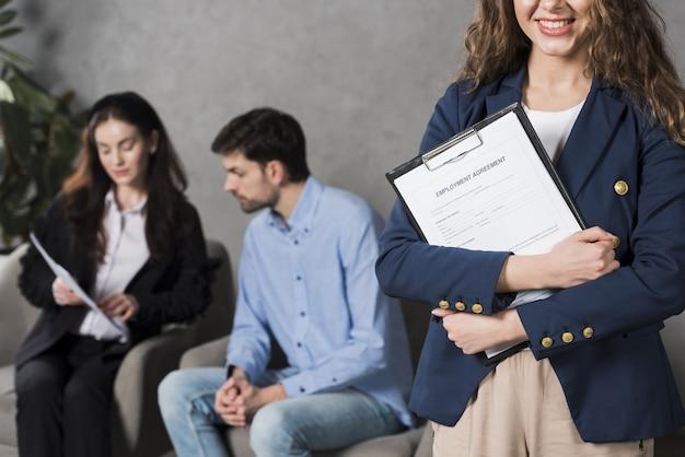 Vorderansicht der frau, die arbeitsvertrag mit potentiellem angestellten hält