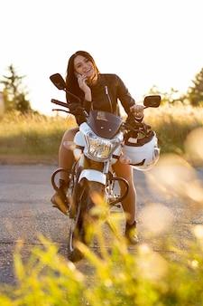 Vorderansicht der frau, die auf smartphone spricht, während auf ihrem motorrad ruht