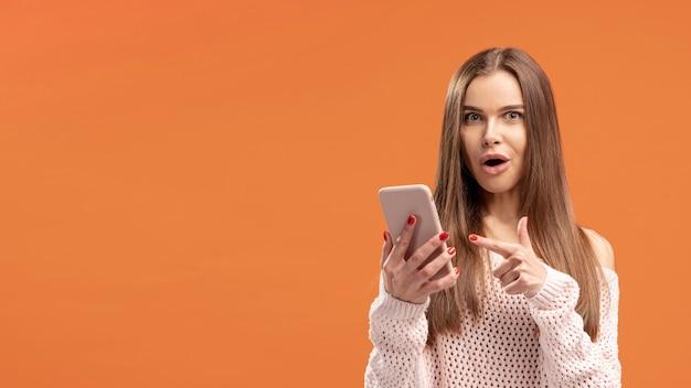 Vorderansicht der frau, die auf smartphone zeigt, das sie hält