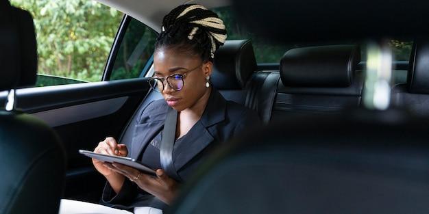 Vorderansicht der frau, die auf tablette schaut, während auf dem rücksitz des autos sitzt