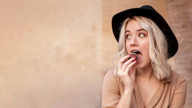 Vorderansicht der frau, die cupcake mit kopienraum isst