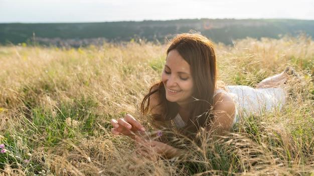 Vorderansicht der frau, die das gras in der natur genießt