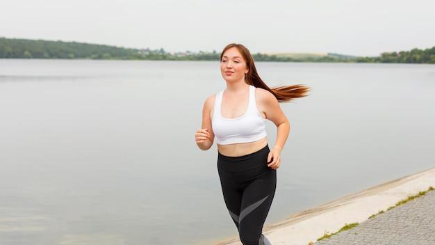 Vorderansicht der frau, die draußen joggt