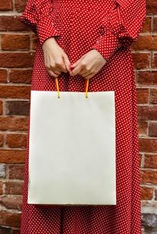 Vorderansicht der frau, die draußen mit einkaufstasche aufwirft