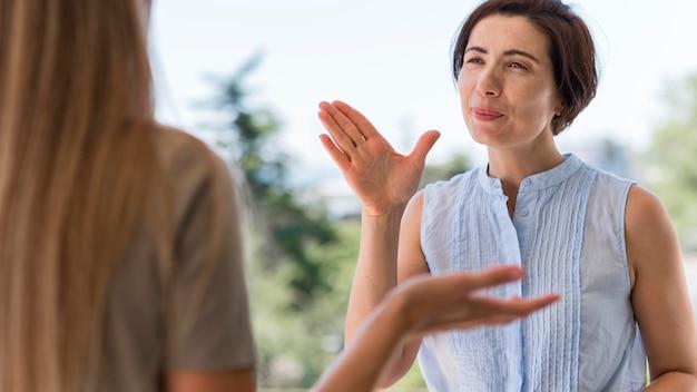 Vorderansicht der frau, die durch gebärdensprache im freien kommuniziert