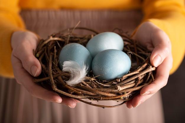 Vorderansicht der frau, die eier für ostern im vogelnest hält