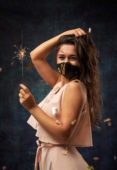 Vorderansicht der frau, die eine maske mit einem feuerwerk trägt